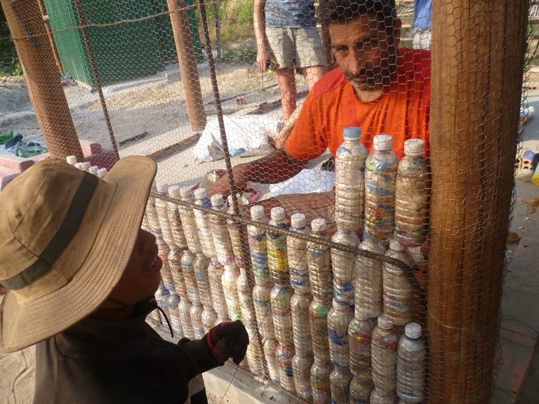 Faramaz helps build the bottle wall